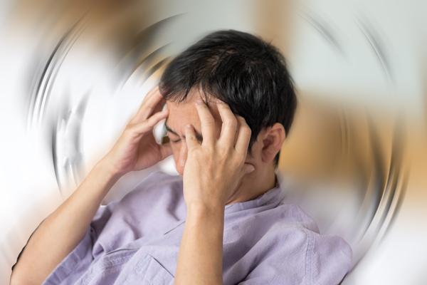 Vertigo illness concept. Man hands on his head felling headache